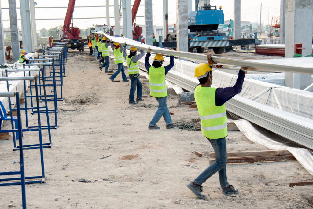 construction workers carrying metal roof panels